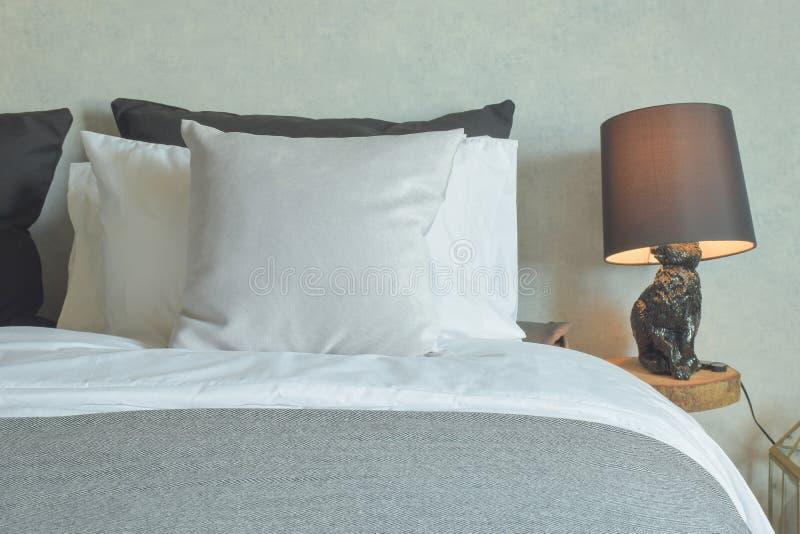 Schoon bed in hotel guestroom met bruine lezingslamp stock foto