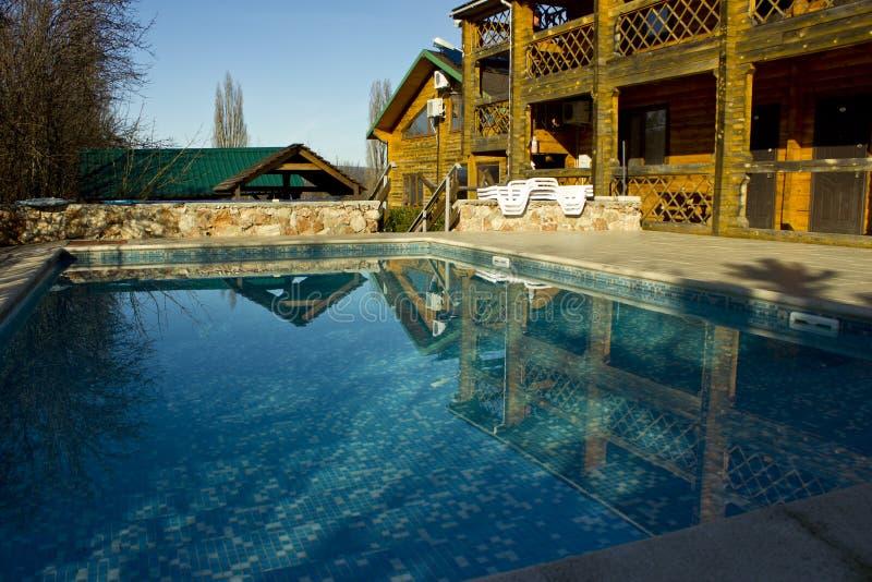 Schoon, duidelijk, blauw water in de pool op het grondgebied van het plattelandshuisje stock afbeelding
