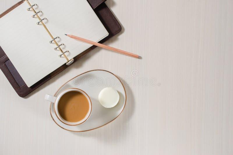 Schoon notitieboekje, kop van koffie en kleurrijke macaron op grijze Desktopmening stock afbeelding