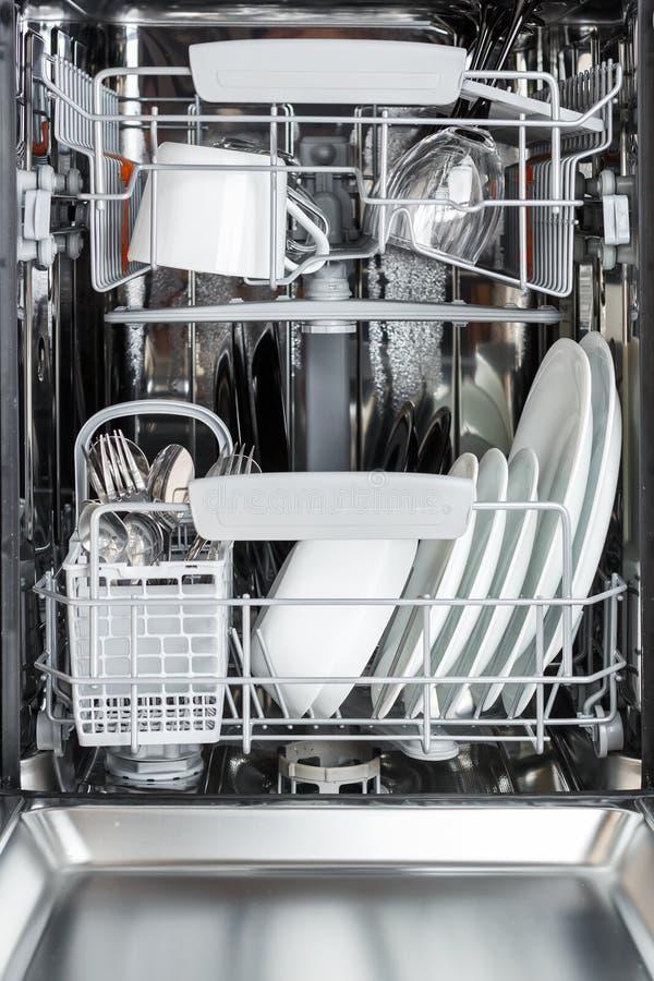 Schoon platen, koppen, glazen en bestek in de afwasmachine daarna royalty-vrije stock afbeelding