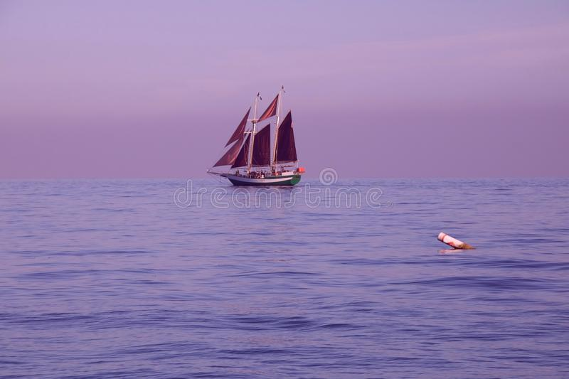 Sailing Ship on a Violet Sea. A schooner sailing on the ocean at dusk as the sun is setting with a violet sky stock photography