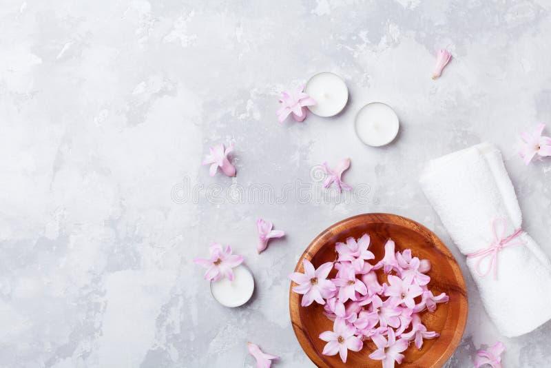 Schoonheid, aromatherapy en kuuroordachtergrond met geparfumeerd roze bloemenwater in houten kom en kaarsen op steenlijst Vlak le stock afbeelding