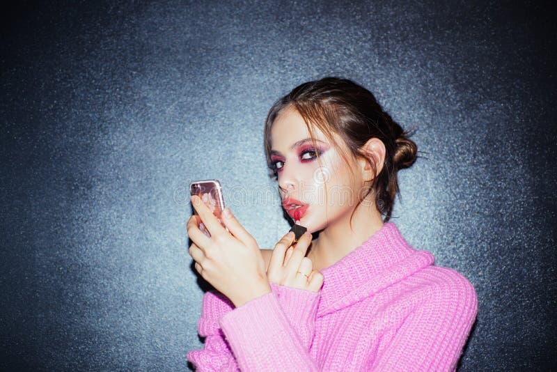 Schoonheid bloger Meisje met lippenstift op lippen de telefoon van het meisjesgebruik als spiegel gezet lipgloss Manierportret va stock foto