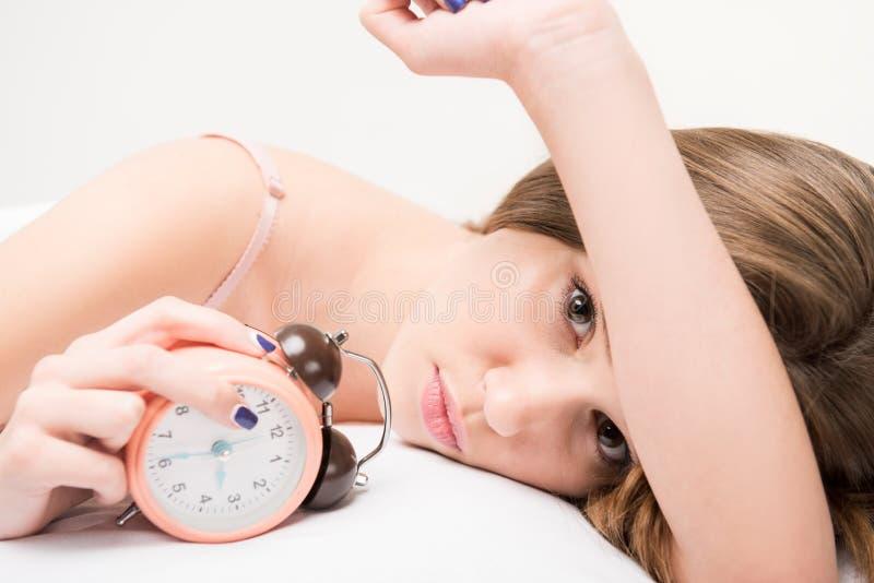 Schoonheid die op het bed met klok liggen stock afbeelding