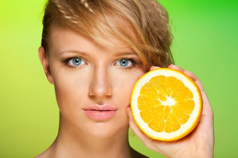 Schoonheid die van een vrouw met sinaasappel is ontsproten stock afbeelding