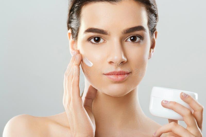 Schoonheid en kuuroordconcept Mooi model die kosmetische room op haar gezicht toepassen Mooie Jonge Vrouw stock afbeelding