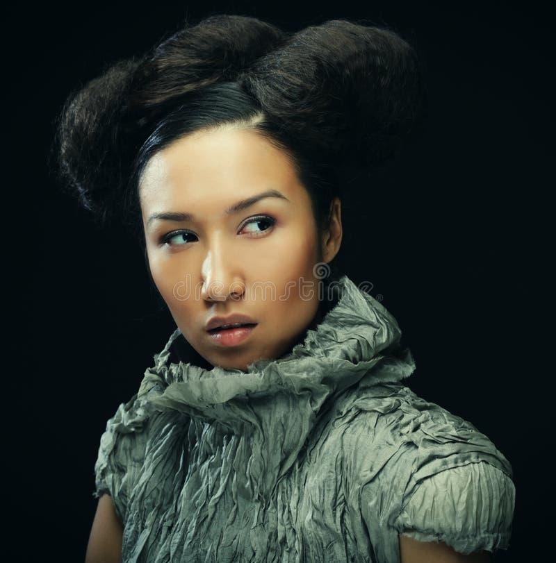 Schoonheid en manierconcept: jonge Aziatische mannequin in grijze kleding tegen zwarte achtergrond royalty-vrije stock afbeelding