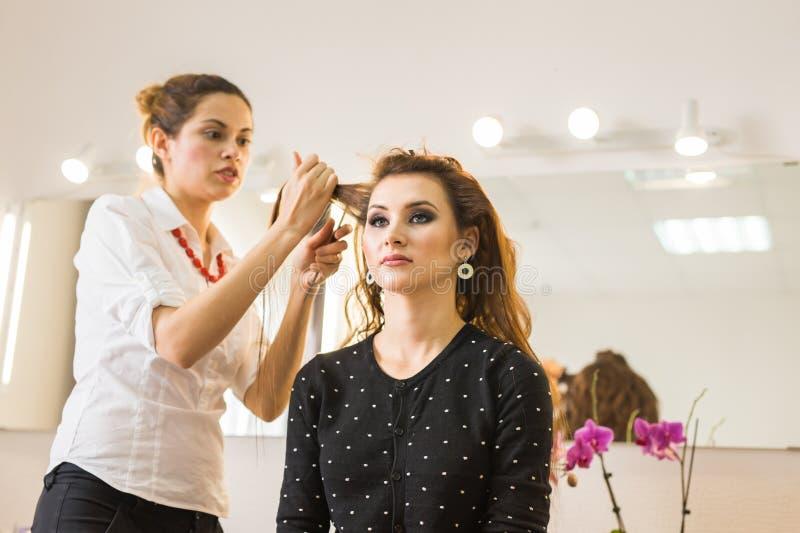Schoonheid en mensenconcept - gelukkige jonge vrouw met kapper bij haarsalon stock foto