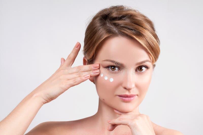 Schoonheid en skincare concept Jonge vrouw die vochtinbrengende crème op gezicht toepassen stock afbeeldingen