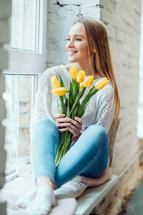 Schoonheid en tederheidsconcept Portret van mooie vrouw met boeket van gele tulpen die op de venster vensterbank en het kijken zi stock afbeelding