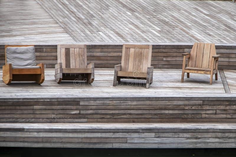 Schoonheid in Hout - de Geassorteerde houten stoelen op z'n gemak zitten op een houten dek bij waterkant stock foto