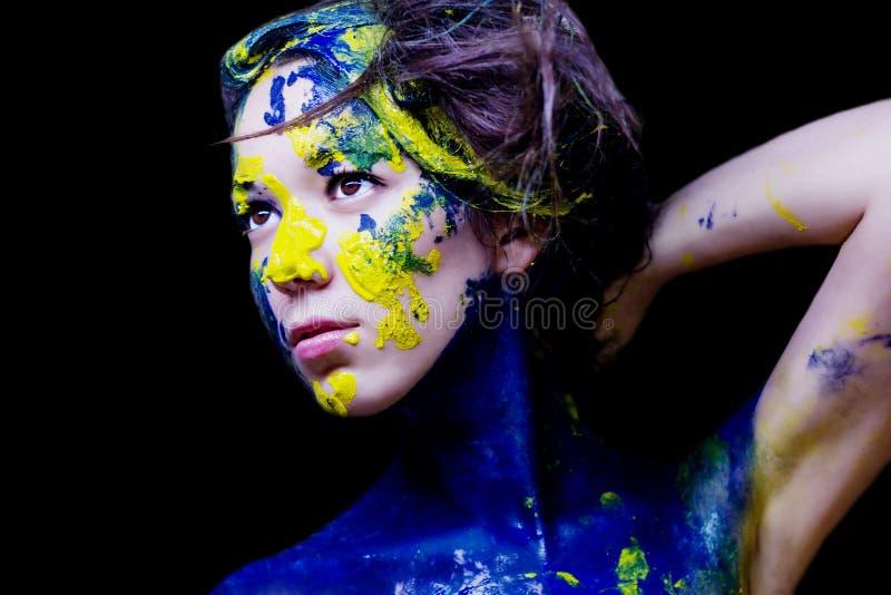 Schoonheid/manierportret van vrouw schilderde blauw en geel op zwarte achtergrond stock foto's