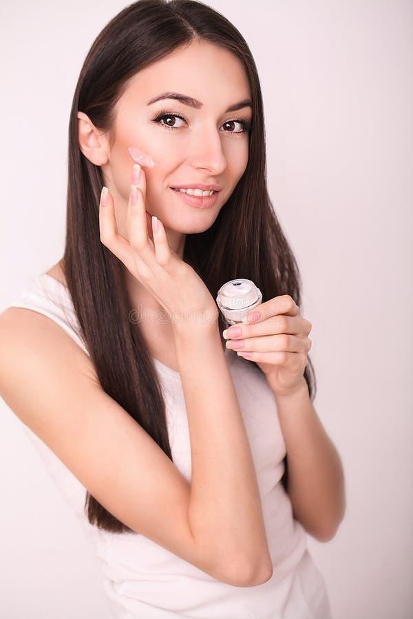 Schoonheid, mensen, schoonheidsmiddelen, skincare en gezondheidsconcept - gelukkige glimlachende jonge vrouw die room toepassen o stock afbeelding