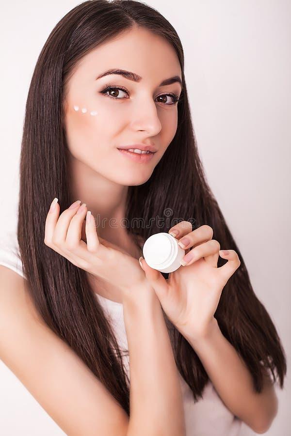 Schoonheid, mensen, schoonheidsmiddelen, skincare en gezondheidsconcept - gelukkige glimlachende jonge vrouw die room toepassen o stock foto