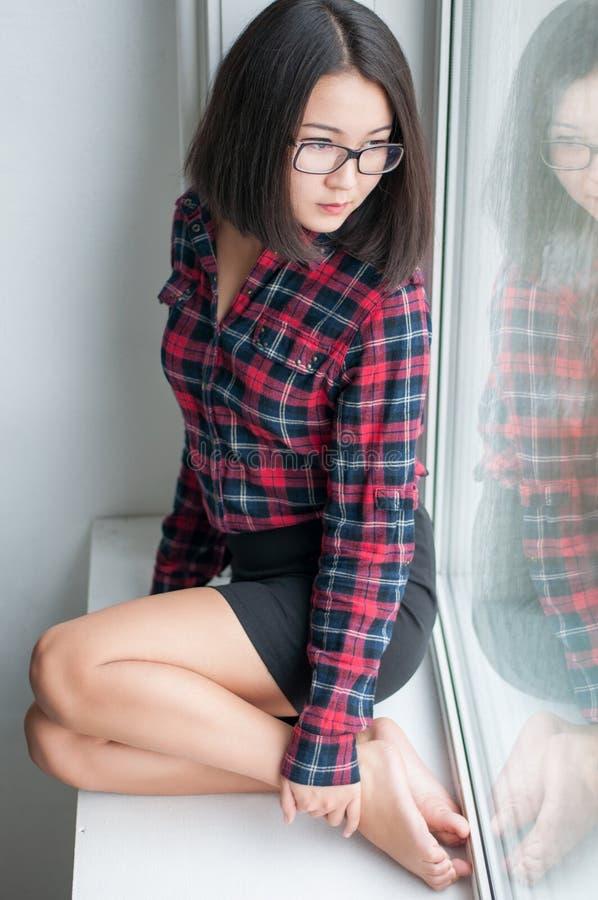 Schoonheids Aziatisch meisje op vensterbank stock foto's