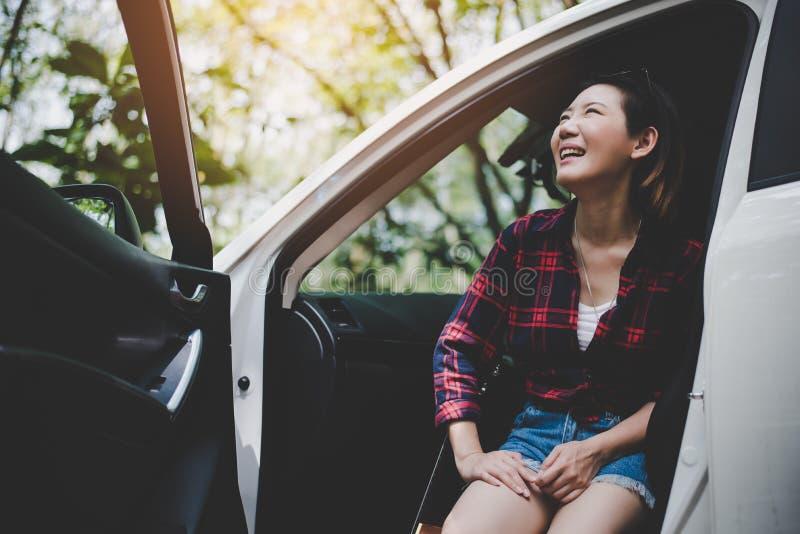 Schoonheids Aziatische vrouw die aan aard kijken en pret hebben bij in openlucht de zomer met Ukelele in witte auto Het reizen va royalty-vrije stock fotografie
