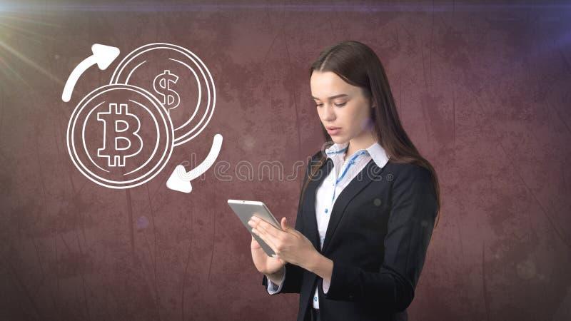 Schoonheids bedrijfsvrouw die zich dichtbij btc embleem bevinden Succesvolle Bitcoin-investering Concept virtuele criptocurrency royalty-vrije stock foto