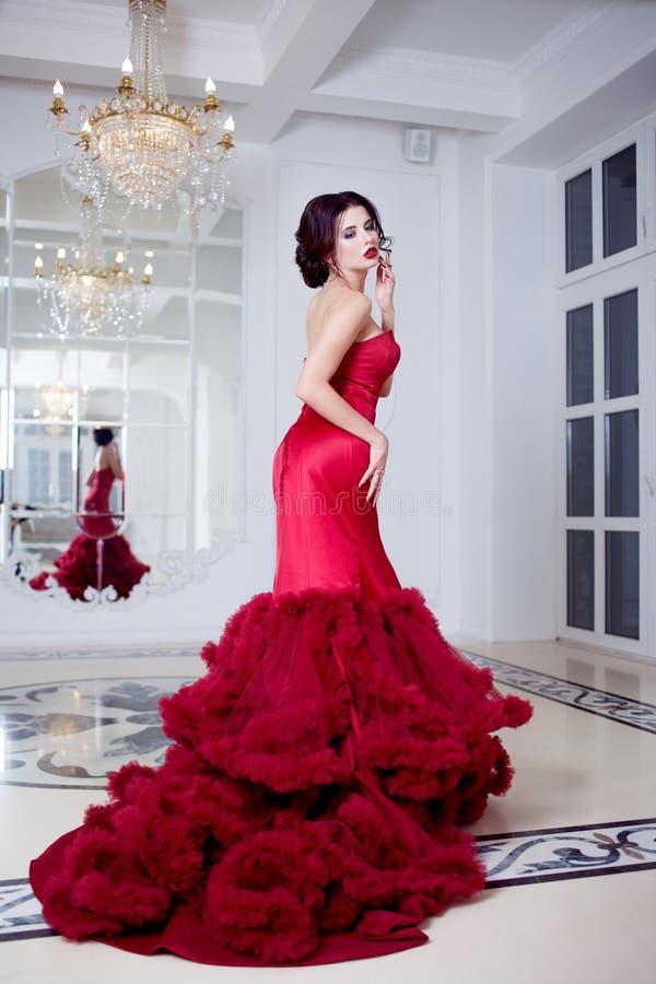 Schoonheids Donkerbruine modelvrouw in avond rode kleding De mooi make-up van de manierluxe en kapsel, volledige lengte stock foto's