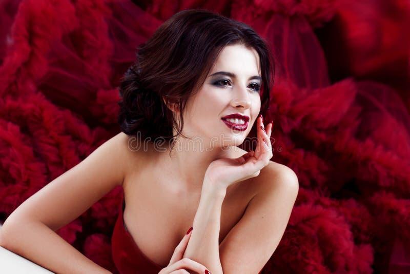Schoonheids Donkerbruine modelvrouw in avond rode kleding Het de mooie make-up en kapsel van de manierluxe stock afbeelding