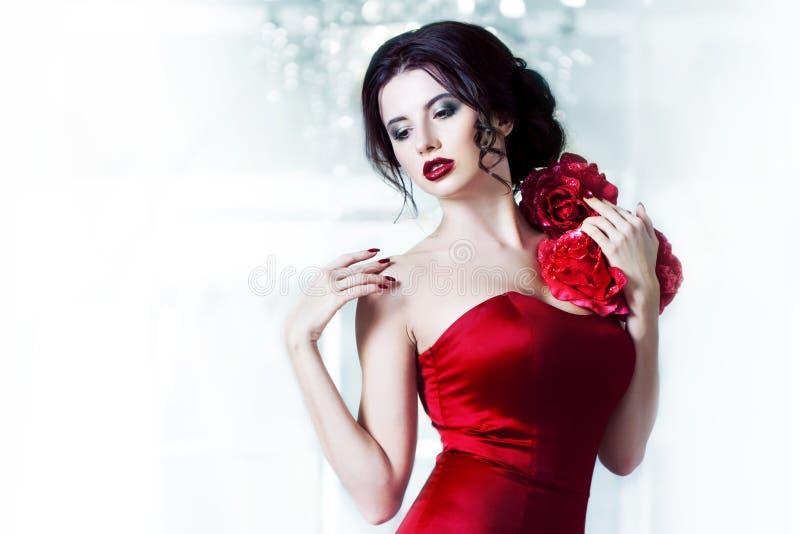 Schoonheids Donkerbruine modelvrouw in avond rode kleding Het de mooie make-up en kapsel van de manierluxe, op de achtergrond van royalty-vrije stock fotografie