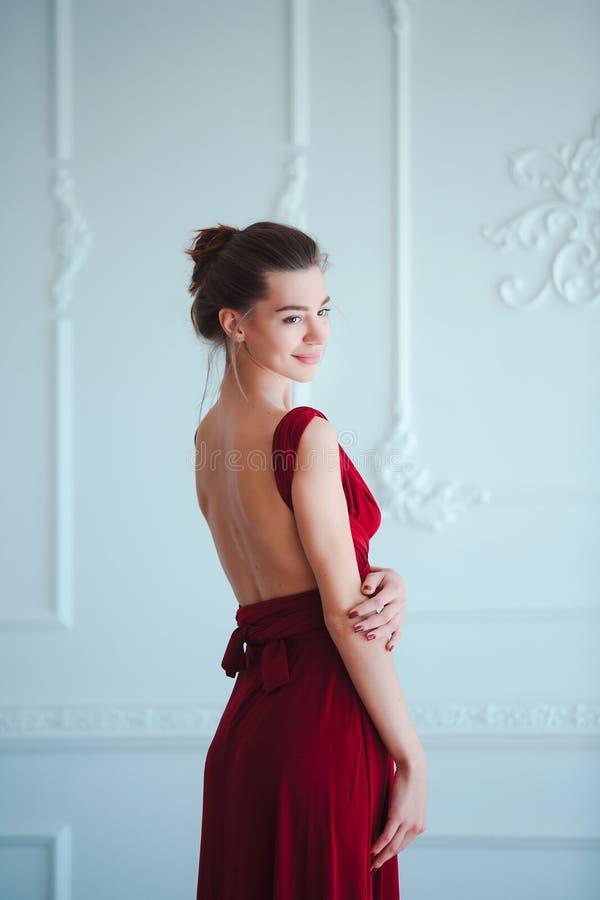 Schoonheids Donkerbruine modelvrouw in avond rode kleding Het de mooie make-up en kapsel van de manierluxe Verleidelijk meisje stock afbeeldingen