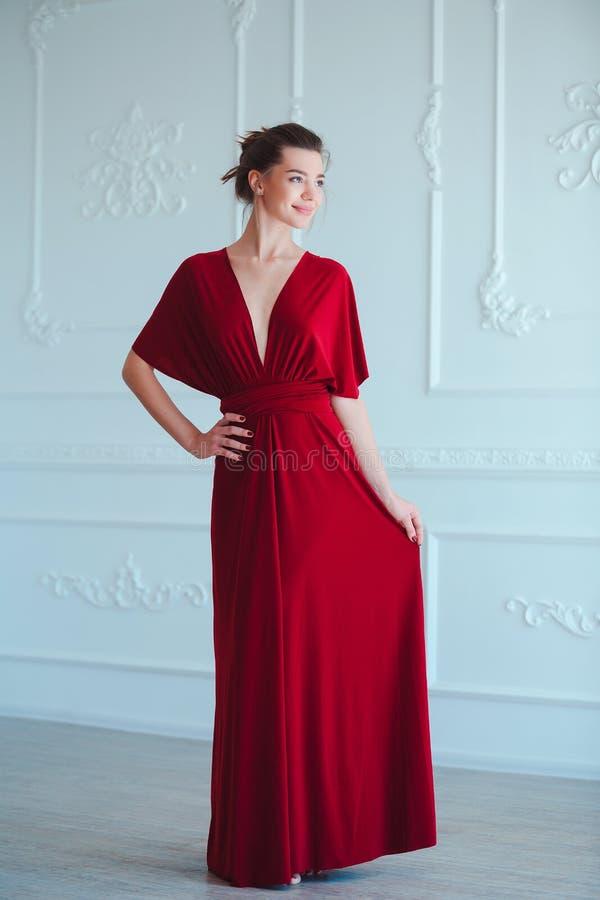 Schoonheids Donkerbruine modelvrouw in avond rode kleding Het de mooie make-up en kapsel van de manierluxe Verleidelijk meisje stock afbeelding