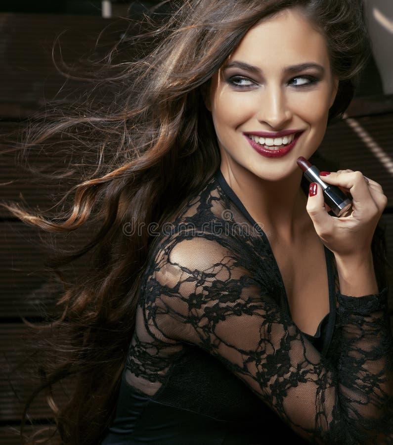 Schoonheids glimlachende rijke vrouw in kant met donkerrode dicht omhoog lippenstift, vliegend haar stock foto