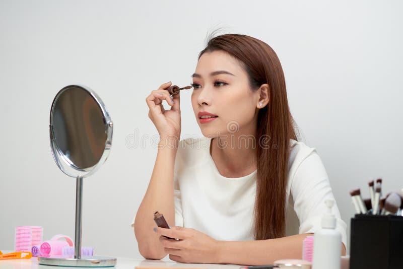 Schoonheids het modeltiener omhoog maken kijken in de spiegel en het toepassen van mascara De mooie jonge vrouw past make-up toe royalty-vrije stock afbeelding