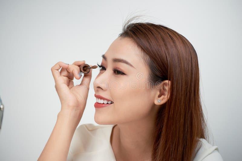 Schoonheids het modeltiener omhoog maken kijken in de spiegel en het toepassen van mascara De mooie jonge vrouw past make-up toe royalty-vrije stock fotografie