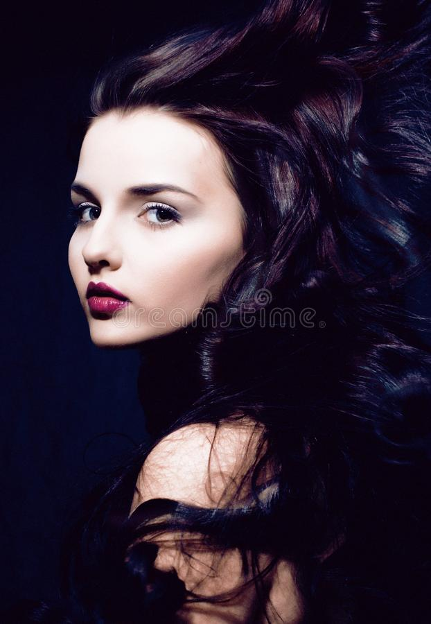 Schoonheids jonge donkerbruine vrouw met krullend vliegend haar, femme fataal stock afbeeldingen