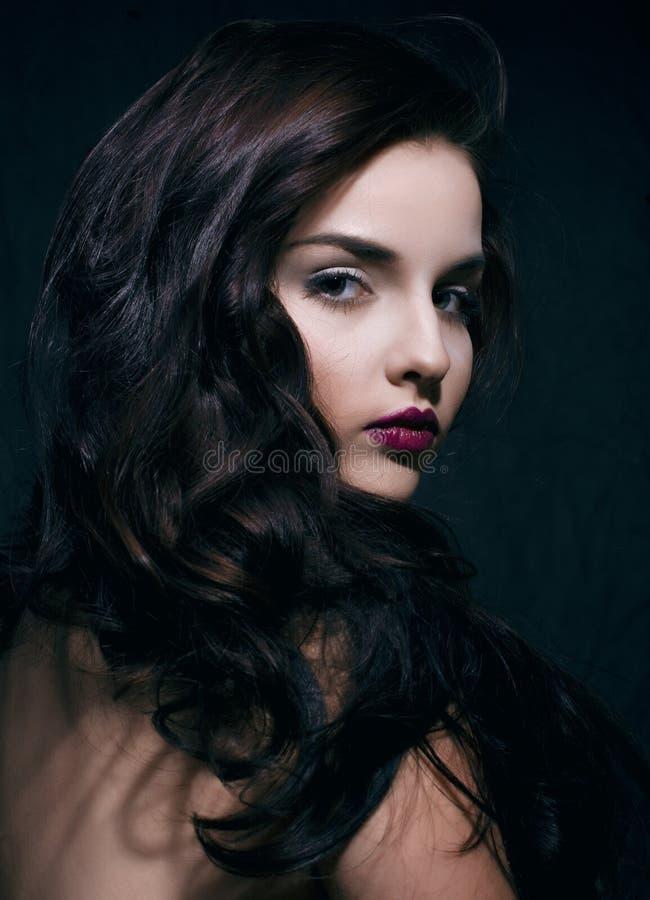 Schoonheids jonge donkerbruine vrouw met krullend vliegend haar, femme fataal op zwarte rustige achtergrond, stock foto
