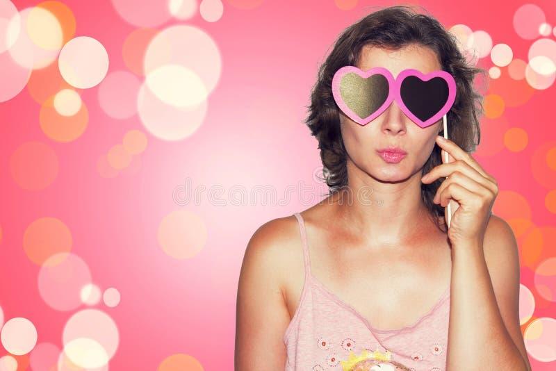 Schoonheids Jonge mannequin Girl met Valentine-hartdocument glazen op roze achtergrond Liefde De gift van de valentijnskaartendag stock afbeeldingen