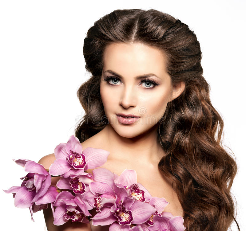 Schoonheids jonge vrouw, luxe lang krullend haar met orchideebloem H stock afbeelding