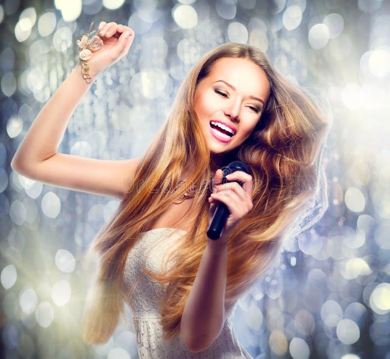 Schoonheids modelmeisje met een microfoon stock foto