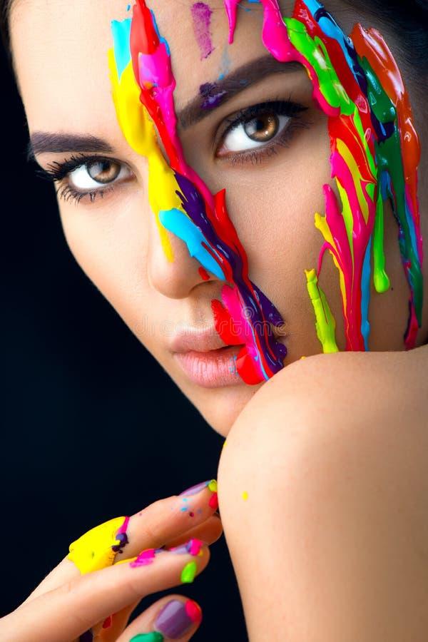 Schoonheids modelmeisje met kleurrijke verf op haar gezicht Portret van mooie vrouw met stromende vloeistofverf stock afbeeldingen