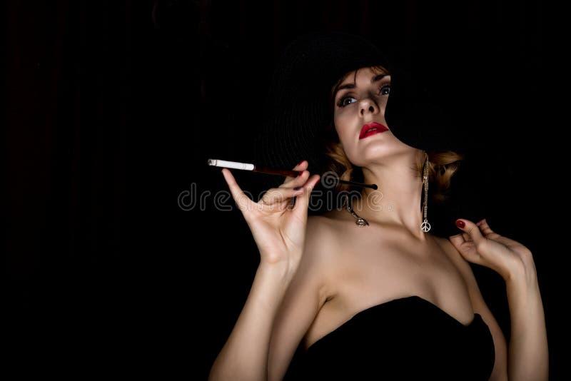 Schoonheids retro vrouwelijk model met professioneel make-up en mondstuk ter beschikking manier uitstekende vrouw op een donkere  stock afbeelding