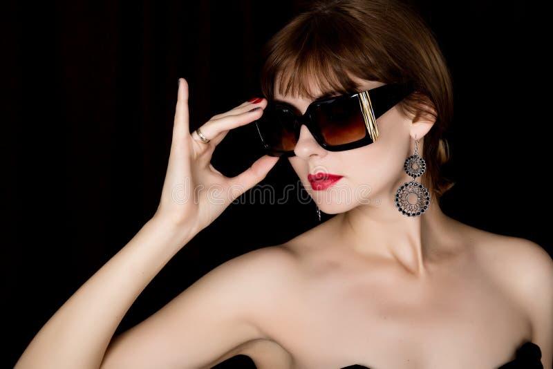 Schoonheids retro vrouwelijk model met professionele make-up in een lange leerhandschoenen, die over groottezonnebril houden stock afbeeldingen