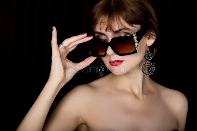 Schoonheids retro vrouwelijk model met professionele make-up in een lange leerhandschoenen, die over groottezonnebril houden stock afbeelding