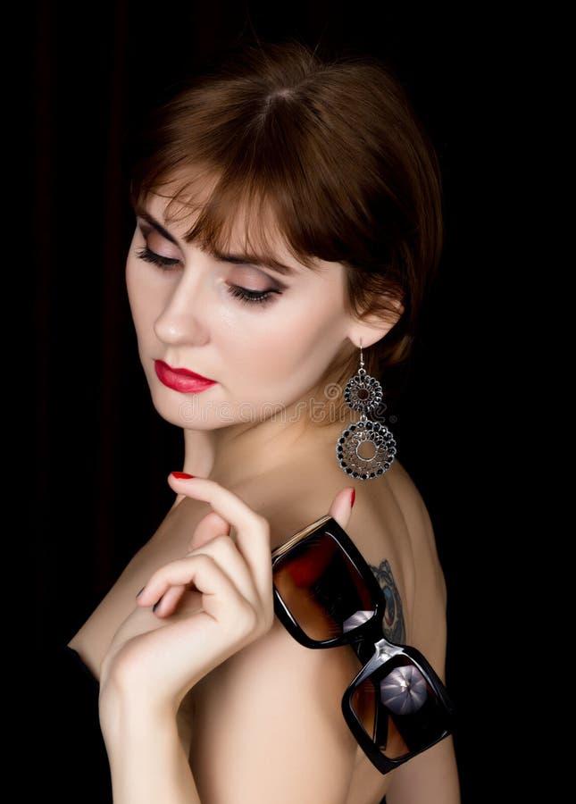 Schoonheids retro vrouwelijk model met professionele make-up in een lange leerhandschoenen, die over groottezonnebril houden royalty-vrije stock foto