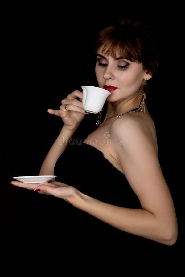 Schoonheids retro vrouwelijk model met professionele make-up, het drinken koffie of thee manier uitstekende vrouw op een donkere  royalty-vrije stock foto's