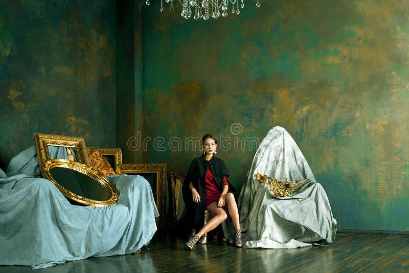 Schoonheids rijke donkerbruine vrouw in luxebinnenland dichtbij lege kaders, stock foto's