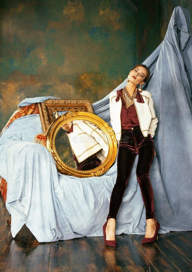 Schoonheids rijke donkerbruine vrouw in luxebinnenland dichtbij lege kaders, uitstekende elegantie royalty-vrije stock fotografie