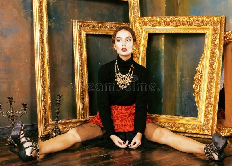 Schoonheids rijke donkerbruine vrouw in luxebinnenland dichtbij lege kaders, uitstekende elegantie stock afbeeldingen