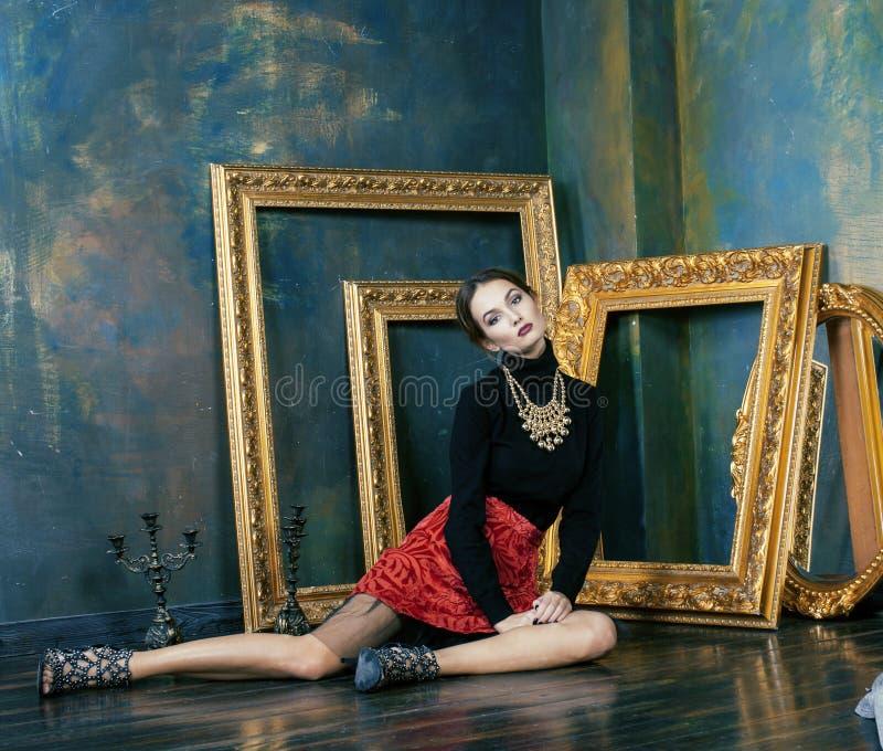 Schoonheids rijke donkerbruine vrouw in luxebinnenland dichtbij lege kaders, uitstekende elegantie dichte omhooggaand stock foto's