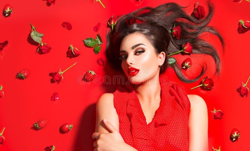 Schoonheids sexy modelmeisje die op rode achtergrond met roze bloemen en aardbeien liggen Mooie donkerbruine jonge vrouw met lang royalty-vrije stock foto's