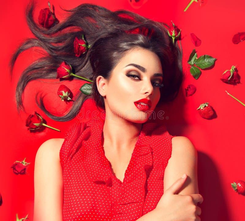 Schoonheids sexy modelmeisje die op rode achtergrond met roze bloemen en aardbeien liggen Mooie donkerbruine jonge vrouw met lang royalty-vrije stock fotografie