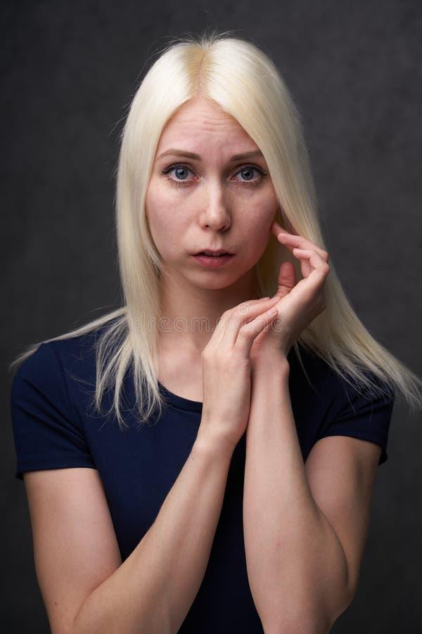 Schoonheids vrouwelijke blond in zwarte vrijetijdskleding op grijze achtergrond stock foto's