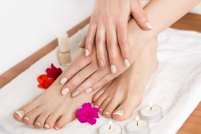 Schoonheids vrouwelijke voeten en handen bij kuuroordsalon op pedicureprocedure en bloemen en kaarsen op witte handdoek stock foto's