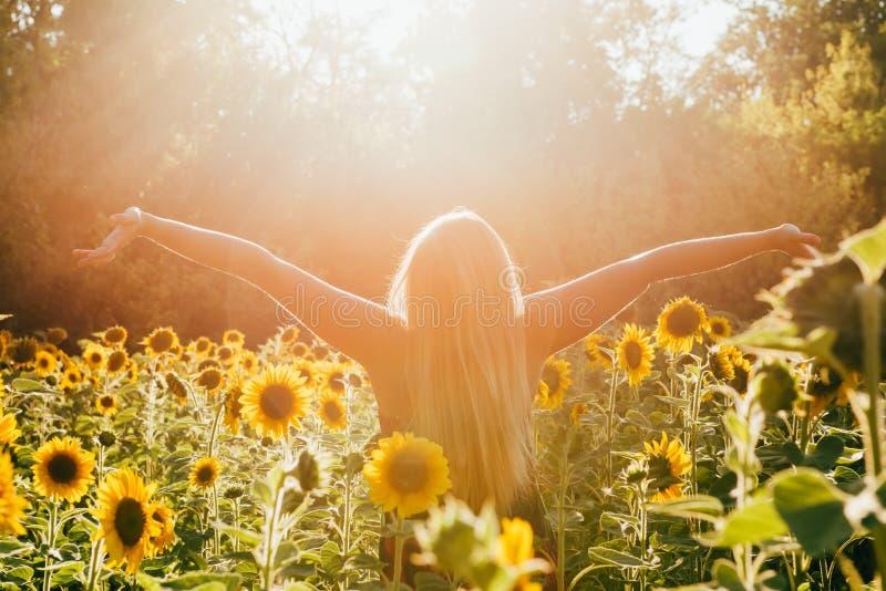 Schoonheids zonovergoten vrouw op de geel Vrijheid van het zonnebloemgebied en gelukconcept royalty-vrije stock foto's