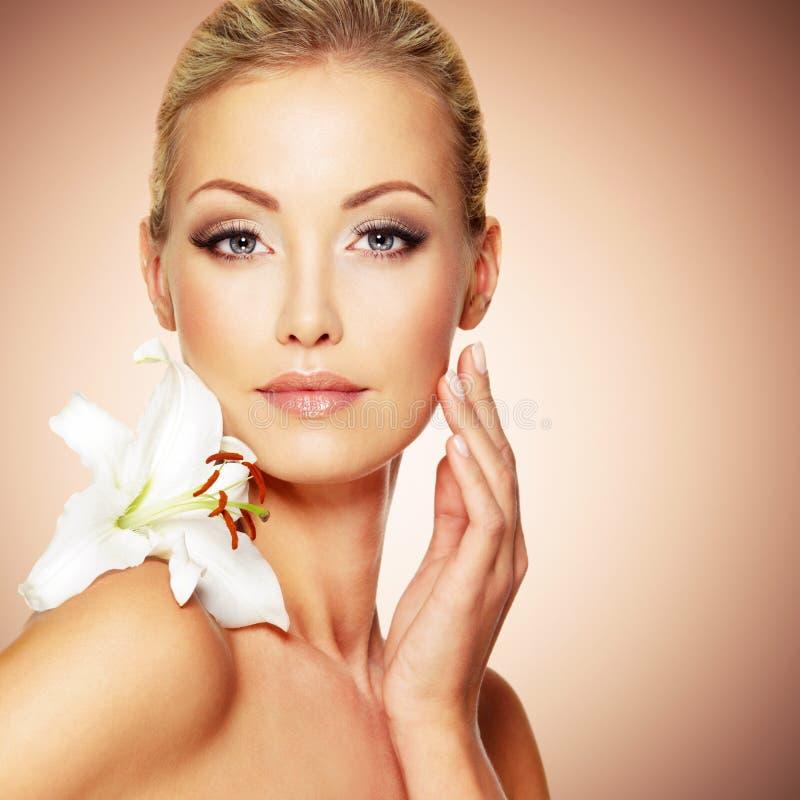 Schoonheids zuiver gezicht van het jonge mooie meisje met bloem stock fotografie